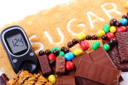 too many: Glucose meter, granulated natural brown cane sugar and a lot of candies and cookies, concept of too many sweets, unhealthy food and diabetes Stock Photo