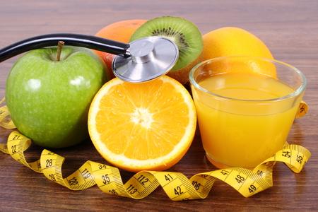 inmunidad: M�dico estetoscopio y cinta m�trica con frutas maduras y vaso de jugo en tabl�n de madera de superficie, manzana naranja pomelo kiwi, estilos de vida saludable y la nutrici�n inmunidad fortalecimiento
