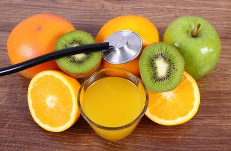 inmunidad: estetoscopio m�dico, frutas maduras y vaso de jugo en un tabl�n de superficie de madera, de color naranja pomelo manzana kiwi, estilos de vida saludable y la nutrici�n inmunidad fortalecimiento
