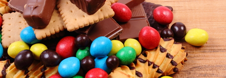 too many: Heap of candies and cookies on wooden table, too many sweets, concept of unhealthy food and reduction of eating sweets