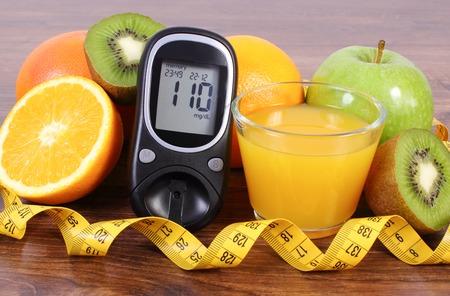 inmunidad: Glucose meter, fresh ripe fruits, glass of juice and tape measure, grapefruit orange kiwi apple, concept of diabetes, healthy lifestyles and strengthening immunity Foto de archivo