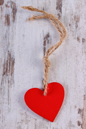 Valentine red heart with twine on old wooden white table, symbol of love, concept of valentines day
