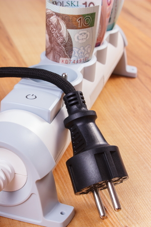 energy costs: Rolls of polish currency money in electrical extension and disconnected plug, power board, concept of saving money on electricity, energy costs