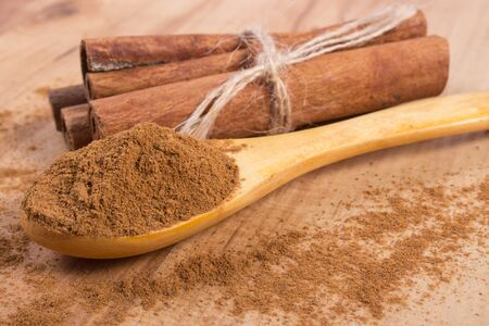 powdery: Powdery cinnamon on wooden spoon and tied cinnamon sticks on wooden table, seasoning for cooking and baking