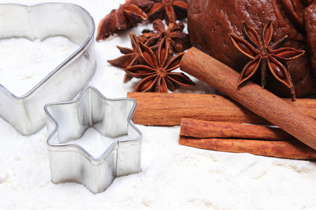 cookie cutters: Spice for baking, cookie cutters, dough for gingerbread and Christmas cookies lying on white flour, concept of baking and christmas time