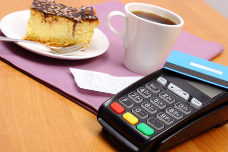 personal identification number: Use payment terminal and credit card for paying in cafe or restaurant, cheesecake and coffee, enter personal identification number, polish receipt, finance concept