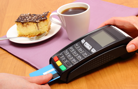 personal identification number: Use payment terminal and credit card for paying in cafe or restaurant, cheesecake and coffee, enter personal identification number, finance concept