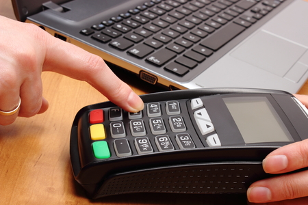 personal identification number: Hand of woman using payment terminal, enter personal identification number, credit card reader and laptop, finance and banking concept