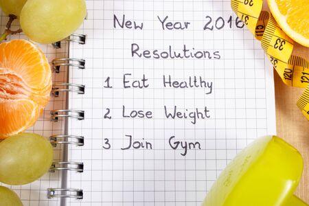 uvas: A�os Nuevos de resoluciones comer saludable, perder peso y unirse a un gimnasio por escrito en el cuaderno, las frutas frescas, las pesas para la aptitud y la cinta m�trica, estilo de vida saludable Foto de archivo