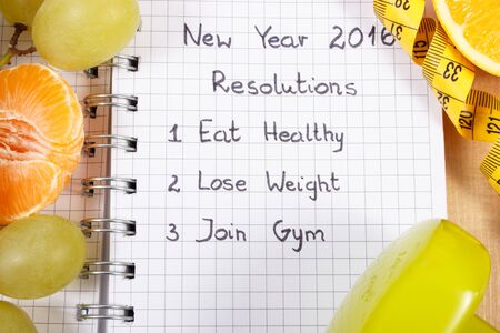 grape fruit: New years resolutions eat healthy, lose weight and join gym written in notebook, fresh fruits, dumbbells for fitness and tape measure, healthy lifestyle Stock Photo