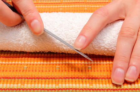 nail file: Woman polishing fingernails with nail file, filing nails, care of hands and manicure Stock Photo