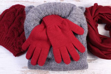 womanly: Woolen clothes for woman on old rustic wooden background, womanly accessories, gloves cap shawl sweater, warm clothing for autumn or winter