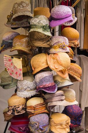 head protection: Collection of handmade hats on stall at the bazaar, womanly accessories, head protection