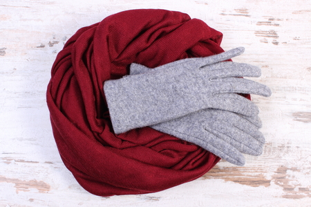 womanly: Pair of grey woolen gloves and burgundy shawl for woman on old rustic wooden background, womanly accessories, warm clothing for autumn or winter