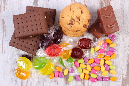 too many: Heap of colorful candies and cookies on old white wooden background, too many sweets, concept of unhealthy food and reduction of eating sweets
