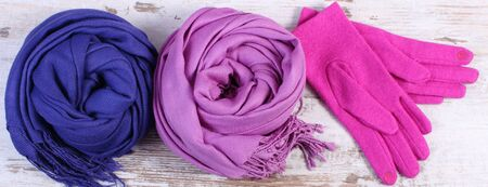 womanly: Woolen gloves and scarves for woman on old rustic wooden background, womanly accessories, warm clothing for autumn or winter