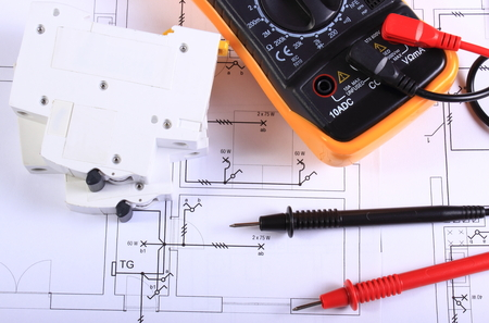 Multimeter with cables and electric fuse lying on construction drawing of house, electrical drawings and tools for engineer jobs Standard-Bild