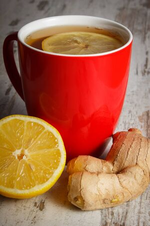 inmunidad: Fresh lemon, ginger and cup of hot tea with lemon on old wooden white table, healthy nutrition, strengthening immunity and alternative therapy