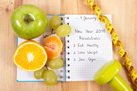 new years resolutions: New years resolutions eat healthy, lose weight and join gym written in notebook, fresh fruits, dumbbells for fitness and tape measure, healthy lifestyle Stock Photo