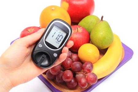 glucometer: Hand of woman with glucometer and fresh natural fruits on cutting board, concept for healthy eating and diabetes