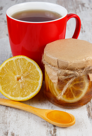 warming therapy: Lemon with honey in glass jar, honey on wooden spoon and cup of hot tea on old wooden white table, healthy food, strengthening immunity and alternative therapy Stock Photo