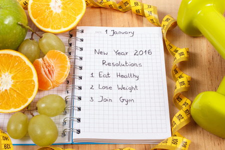 fitness goal: New years resolutions eat healthy, lose weight and join gym written in notebook, fresh fruits, dumbbells for fitness and tape measure, healthy lifestyle Stock Photo
