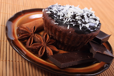desiccated: Homemade delicious fresh baked chocolate muffins with desiccated coconut, pieces of chocolate and star anise lying on plate Stock Photo