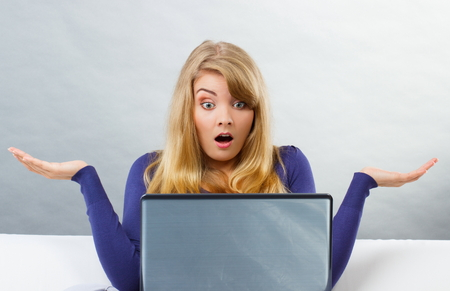 Frustrated and scared woman shrugging shoulders with raised hands sitting on sofa and looking at laptop screen, computer problem