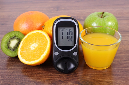 immunity: Glucose meter, fresh ripe fruits and glass of juice on wooden surface, concept of diabetes, healthy lifestyles nutrition and strengthening immunity