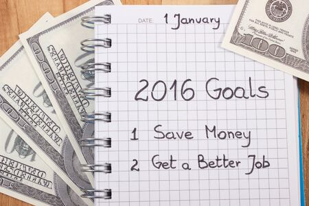 better: New years resolutions save money and get better job written in notebook and currencies dollar