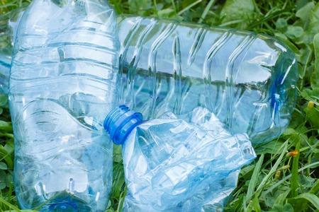botar basura: Botellas aplastadas plásticas de agua mineral en el césped en el parque, el concepto de protección del medio ambiente, basura del medio ambiente