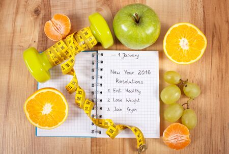exercise weight: New years resolutions eat healthy, lose weight and join gym written in notebook, dumbbells for fitness with tape measure, concept of healthy lifestyle