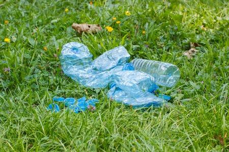 botar basura: Botellas de pl�stico triturado de agua y tapas de botellas de minerales en el c�sped en el parque, el concepto de protecci�n del medio ambiente, basura del medio ambiente Foto de archivo