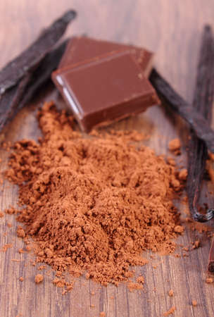 powdery: Powdery cocoa, pieces of dark chocolate, fresh fragrant vanilla sticks pods on wooden surface plank, seasoning ingredients for cooking or baking Stock Photo