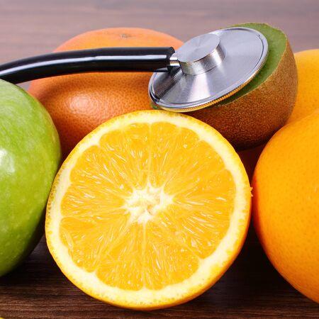 inmunidad: M�dico estetoscopio y frutas maduras en el tabl�n de la superficie de madera, kiwi naranja pomelo, estilos de vida saludable y la nutrici�n inmunidad fortalecimiento Foto de archivo