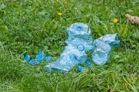 tirar basura: Crushed plastic bottles of mineral water and bottle caps on grass in park, concept of environmental protection, littering of environment