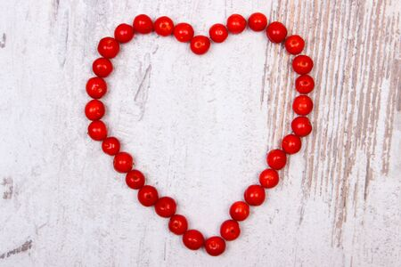 Valentines heart of red viburnum on old wooden rustic background, symbol of love Stock Photo