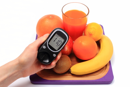 inmunidad: Hand with glucometer, fresh ripe natural fruits and glass of juice on cutting board, concept for diabetes, healthy nutrition and strengthening immunity