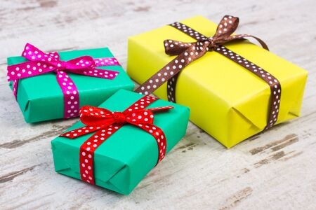 old desk: Wrapped colorful gifts for Christmas, birthday or other celebration on old wooden white plank Stock Photo
