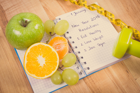 healthy lifestyle: Vintage photo, New years resolutions eat healthy, lose weight and join gym written in notebook, fresh fruits, dumbbells for fitness and tape measure, healthy lifestyle