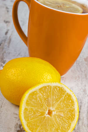 warming therapy: Fresh lemon and cup of hot tea with lemon on old wooden white table, healthy nutrition, strengthening immunity and alternative therapy