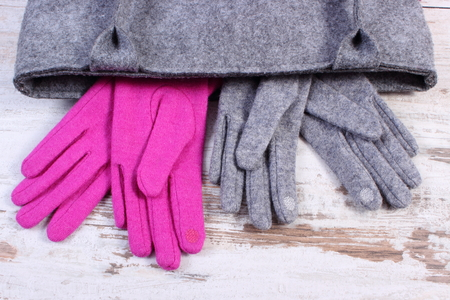ladylike: Woolen gloves for woman and handbag on old rustic wooden background, womanly accessories, warm clothing for autumn or winter