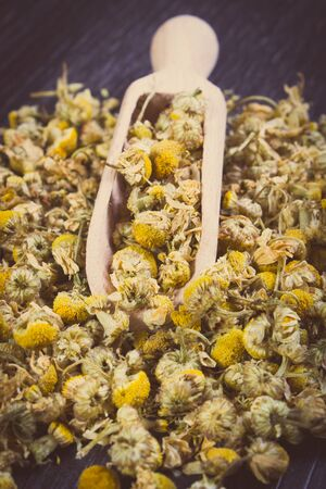 herbalism: Vintage photo, Heap of dried chamomile with wooden spoon lying on wooden surface, concept of healthy nutrition, herbalism and alternative medicine Stock Photo