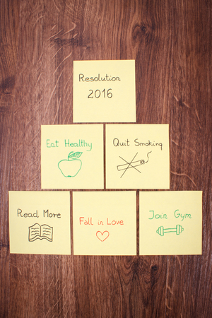 new years resolution: New years resolution written on yellow sheet of paper lying on wooden background Stock Photo