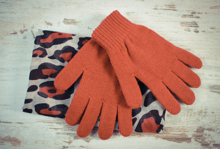 ladylike: Vintage photo, Pair of burgundy woolen gloves and colorful shawl for woman on old rustic wooden background, womanly accessories, warm clothing for winter