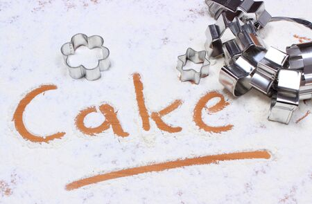 cookie cutters: Word cake written in white flour and set of cookie cutters, concept of baking Stock Photo