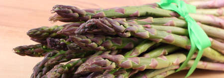 immunity: Bunch of fresh green asparagus on wooden surface, concept of healthy food, nutrition and strengthening immunity Stock Photo