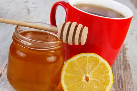 warming therapy: Fresh lemon, honey in glass jar and cup of hot tea on old wooden white table, healthy food, strengthening immunity and alternative therapy Stock Photo