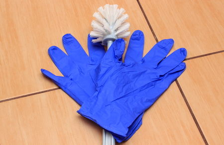 duties: Accessories for cleaning bathroom on ceramics flooring, brush, glove, concept for house cleaning and household duties