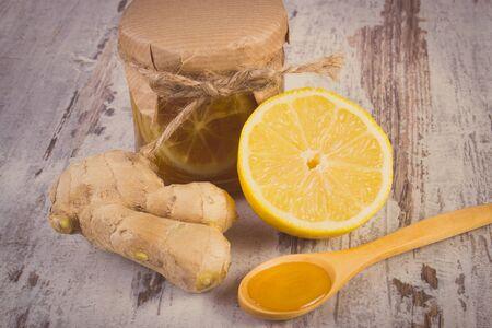 inmunidad: Foto de la vendimia, de lim�n con miel en frasco de vidrio, la miel en la cuchara de madera y el jengibre en la vieja mesa de madera blanca, el concepto de la comida sana, la nutrici�n y la inmunidad fortalecimiento